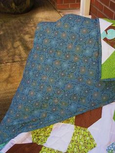 Rich turquoise and brown, touched with shades of green make this an eye popping quilt. 100% cotton and high 80/20 batting. The darker turquoise backing adds contrast to the bright front.  57.5 X 58.5