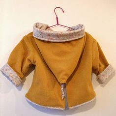 Veste magique moutarde – Anisbee Magic jacket for baby, reversible & zip closure in the back. sewing pattern & tutorial & in french here : santalili. Baby Outfits, Kids Outfits, Baby Couture, Couture Sewing, Baby Clothes Quilt, Sewing Clothes, Sewing Patterns For Kids, Clothing Patterns, Kids Coats