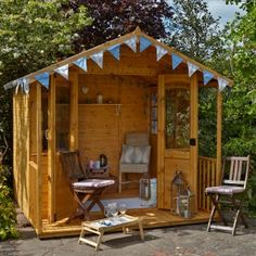 contemporary Garden room Cute small decorated wooden garden room with chairs and surrounded by bush