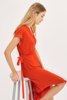 Summer styling couldn't be any easier than this chic wrap dress in red. Detailed with a v-neckline, modern asymmetric hem and belt detail to cinch in the waist. Finish the look with heeled mules for a day-to-night feel.