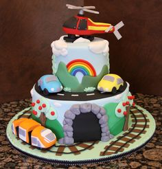 Mom made a composite print of several different cakes put together to come up with this design that she wanted me to replicate.  The base is 10 and the top tier is 5 covered in fondant.  All accents cars, train and helicopter are all fondant.