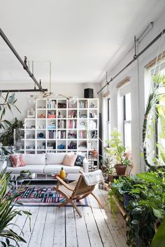 Modern bohemian living room in a loft featuring cube bookcase storage and lots of plants - Global Decor & Boho Decorating Ideas