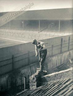 Workers begin knocking down houses to create the Paxton Road Stand. 1936