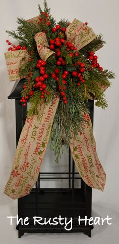 Our lantern swags are great way dress up any lantern! This swag is decorated with burlap ribbon, various greens, and berries . They are versatile and can be used on a wreath, mirror, and so many other places! The swag measures approx. 12 W x 25L. They simply attach with wired chenille. Lantern is NOT included in sale. *Please note our handmade items may vary slightly.