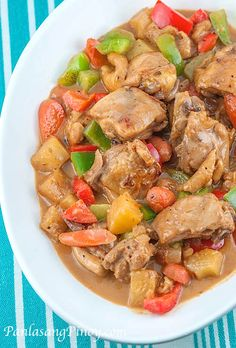 Pininyahang manok_1½ lbs. chicken, cut into serving pieces 1 (14 oz.) can pineapple chunks 1 small red bell pepper, sliced 1 small green bell pepper, sliced 1 cup coconut milk 1½ tablespoons fish sauce 2 small carrots, sliced diagonally 1 small onion, diced 1 medium plum tomato, diced 1 teaspoon minced garlic ¼ teaspoon ground black pepper 3 tablespoons cooking oil
