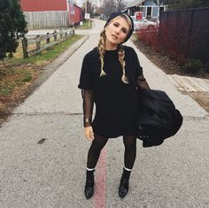 Punky, relaxed fall winter #ootd street style. Black T shirt dress, black tights, black boots, beanie with ears, long braids, pigtail braids, smiley eye, big jacket, faux fur bomber