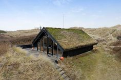 This little cottage is nestled among the sand dunes on the northern coast of Denmark. Its vernacular appearance and sod roof might fool some into thinking that it is a historic home, but the fully-...