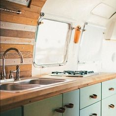 Renovated Airstream Interior with Reclaimed Wood and Mint Cabinets with Leather Handles