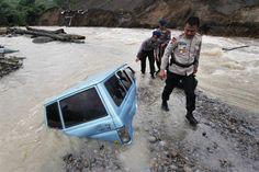 Indonezja - policjant obok wraku samochodu, który zsuną się do rzeki w wyniku osunięcia drogi spowodowanego trzęsieniem ziemi w prowincji Aceh (fot. Ade Sinuhaji/Xinhua/ZUMAPRESS.com)