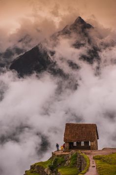 Clouds rise around and over the gatekeepers hut in Machu Picchu, Peru. The Peruvian highlands rise in the background