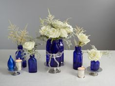 Blue and White Holiday : To liven up the traditional blue and white holiday theme, use vintage glass bottles for vases. Using elegant flowers like roses elevates the look. You could also repurpose glass soda and water bottles that come in blue shades as the vases instead.