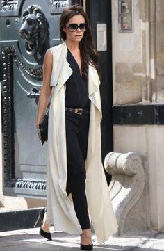 Victoria Beckham en combinaison noire et long manteau écru.