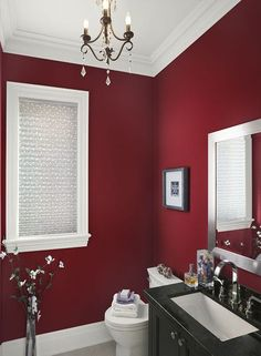 contemporary dark red bathroom with white accents, black bathroom cabinets, and small chandelier...