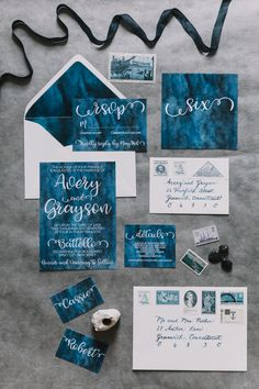 Elevated Nautical themed wedding invitations: deep navy watercolor with contrasting white envelopes, navy calligraphy, and blue vintage stamps. Coordinating place cards, table numbers, and menus!