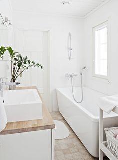 Yläkerran kylpyhuoneessa on kaunis valo. Iso amme on Svedbergsin. Allaskaappi on Ikeasta, ja sen päällä on Kvikin tammitaso. Ikean hoitopöytä on maalattu valkoiseksi. Hanat ovat Oraksen. Seinien valkoisen mattalaatan koko on 25 x 40 senttiä.