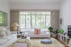 Sala de estar clean tem sofás, tapete e cortinas brancas. Pontos de cor em plantas, almofadas e pufe.