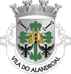 """Civic heraldry of Portugal - Brasões dos municípios Portugueses - Escudo de prata, com uma cruz florenciada de verde, carregada por um castelo de ouro aberto e iluminado de negro. A cruz é acompanhada em chefe por duas travas de negro, uma em banda e outra em contrabanda apontadas ao centro e em contra-chefe por duas águias de negro, abertas e afrontadas. Coroa mural de prata de quatro torres. Listel branco com os dizeres a negro : """" VILA DO ALANDROAL"""".  August 10, 1936."""