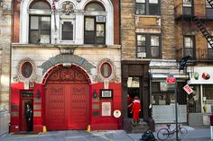A few Santacon revelers enter an apartment house as a firefighter from the station next door looks outside.