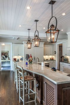 Copper lanterns with black bails over 15-foot island. Traditional French country kitchen.