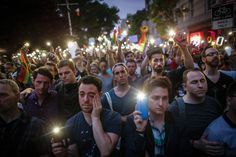 People hold candles and lights during a vigil outside the Stonewall Inn.