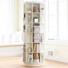 """Revolving bookcase, create a rotating display of your favorite things with this unique, space-saving tower. 25.5"""" diameter, 69.5"""" high. Crafted with a kiln-dried hardwood frame.Swivels 360°. 42 fixed cubbies in five different sizes. Finished by hand in PBteen White paint. Could use this in several ways."""