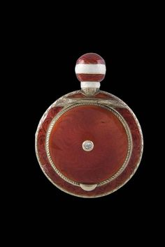 "A silver-gilt and guilloché enamel scent bottle with pill box. The body with translucent red over sunburst ground. The lid set with a diamond. The border with engraved foliage frieze. The reverse set with a gold head of an elephant. The spherical cover with translucent white and red enamel, minor chipped. Gilt interior. Stamped with assayer's mark, 84 standard and master's mark ""AR"". St. Petersburg, Fabergé, 1908-1917. 6,5 cm long."