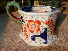 Spectacular early Gaudy Welsh ironstone cider mug with unusual flared base and bold floral decoration. Octagonal with snake handle. Pattern unknown. Some crazing but no chips or cracks. 3 1/2″ H x 4 1/4″ dia. Circa 1830. This is a rare one. Must see other images to truly appreciate. $465 http://www.bluelineantiques.com/wp-content/uploads/2009/08/Gracie-and-antiques-036.jpg