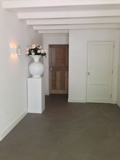 Entree met betonstuc vloer. Deze vloer ligt overigens door de gehele benedenverdieping. De houten rol deur biedt toegang tot de living. www.molitli-interieurmakers.nl