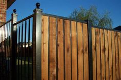 Iron ornamental fence wit straight rail top with (maybe inserted in spaces. Places where privacy isn't an issue are left just iron w/o addition of wood pickets. This might be a compromise for us.