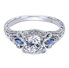 Gabriel & Co. Amavida Platinum Victorian Halo Engagement Ring accented with quality sapphires. This vintage styled engagement ring has simplicity in style but holds much statement and beauty in its details. We love all the little diamonds put all throughout this beautiful piece. The stunning sapphire stones make the diamond center stone pop!