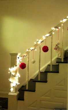 Holiday banister with felt poms and Snow White looking slightly miserable.