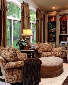 pretty arched windows, comfy furnishings, window panels on medallions, glazed bookcase with contrast back color