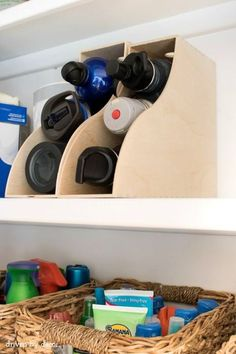 """We've all had that moment when you open up the cabinet and all the reusable water bottles you've ever owned come tumbling that. Say """"enough"""" and become a convert to this new way of storing them: inside a magazine holder. See more at Driven By Decor »"""