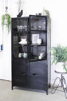 Smalle, zwarte buffetkast Deze industriële buffetkast geeft een zee aan opbergruimte. Door het glas in de deuren kan je alles overzichtelijk opruimen. Of het nou gaat om je boeken collectie, een mooie verzameling, je servies of je garderobe / schoenen, deze stoere ijzeren kast heeft een toepassing voor alles wat je wilt. De dichte onderste …