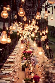 Outdoor Rustic theme. Beautiful hanging light bulbs and floral arrangements.