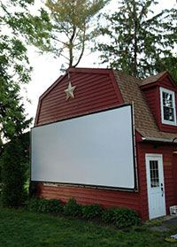 """""""Purchased the 9x21 bungee and grommet screen with the blackout cloth. We've transformed the side of our barn into an outdoor movie theater during weekends in the summer. The screen is high quality and the set up was quick and easy. All in all, it's everything we hoped for and then some. Well done.""""  —Edward K. 