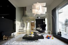 Floating stairs, white walls and a mordern light fixture...perfect! Photography by Eveliina Mustonen