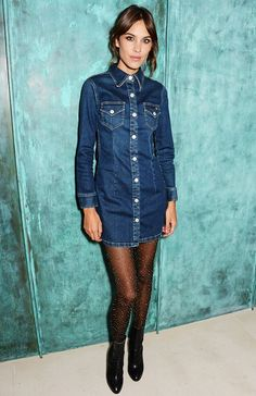 Alexa Chung wears a button-down denim dress, sparkly tights, and black boots