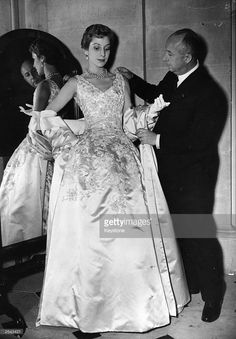 Christian Dior (1905 - 1957) French couturier, born in Normandy with one of his own designs, a satin evening gown called Blenheim.