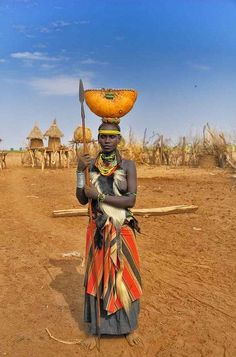Africa | Dessanech woman from Omo Valley, Ethiopia | The buildings behind the woman are sorghum silos. The gourd on her head is for carrying water. | Rpd Waddington