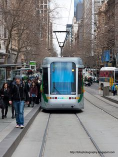 Melbourne trams, one of which is in front of the Anglican Cathedral in Melbourne, Australia in September 2010