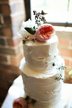 Simple rustic looking wedding cake topped with peonies