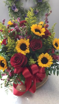 Sunny sunflowers, gorgeous red roses, snapdragons, solidago and lush greenery pop against the white wicker basket.