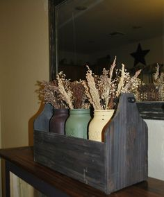 Old wooden toolbox with painted mason jars…add some dried naturals for a nice subtle country look or some hydrangeas if your in to that foofy stuff! Change out the filler for the holidays!