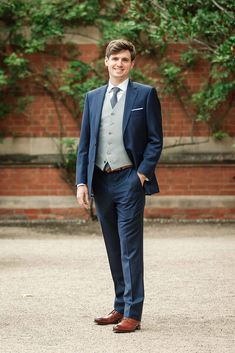 Groom wears a navy suit and grey waistcoat. Images by Becky Harley