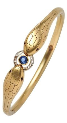 An Art Deco 18kt Gold Snake Bracelet, France, circa 1920. The hinged bangle designed as a pair of snakes clutching a synthetic sapphire and rose-cut diamond ring, guarantee stamps. #ArtDeco #bracelet