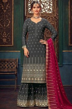 Specifically designed for a stylish lady like you is this charcoal grey georgette sharara suit which will instantly catch your fancy. This sweetheart neckline and full sleeve dress embroidered with stone and zari work. Present with georgette sharara pants in charcoal grey color with ruby pink georgette dupatta. Sharara pants has zari work. Dupatta also elaborated using zari work. #shararasuits #malaysia #Indianwear #weddingwear #andaazfashion Sharara Suit, Salwar Kameez, Indian Attire, Indian Wear, Plus Size Lehenga, Pantalon Cigarette, Costume, Anarkali, Pakistani Sharara