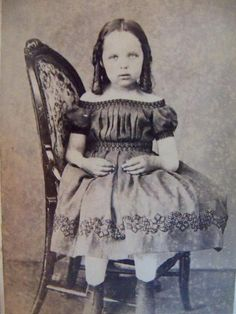 Victorian era Post-mortem photo, 19th century  Like a delicate china doll sitting on a shelf, this child is not sitting as one normally would, but is turned to the side so that a stand can be used to hold her in place. The stand is plainly visible underneath the chair. Her thin little arms have no muscle tone whatsoever and have been carefully placed into position. The bottom of her elegant dress has been placed into a strange position as it actually extends well beyond the seat of the…