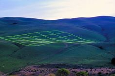 """""""Luminous Earth Grid"""" is an outdoor art installation by Stuart Williams. It is a project co-sponsored by The New York Foundation for the Arts and Intersection for the Arts (San Francisco). An array of 1,680 energy-efficient fluorescent lamps, swept over 10 acres of undulating landscape.   http://www.behance.net/scw"""
