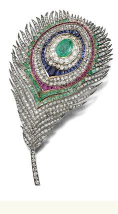 MAGNIFICENT AND RARE GEM-SET AND DIAMOND BROOCH, MELLERIO Realistically designed as a peacock feather set with variously cut emeralds, French-cut sapphires and rubies, highlighted with circular-, single- and rose-cut diamonds, to a flexible stem, mounted in silver and gold, signed Mellerio, Paix, French assay and maker's marks.
